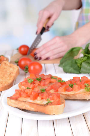 Delicious bruschetta with tomatoes on plate on table close-up photo