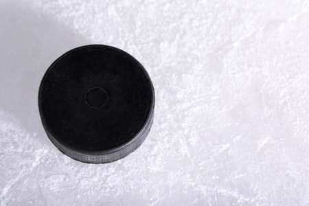 ice hockey puck: Black hockey puck on ice rink background