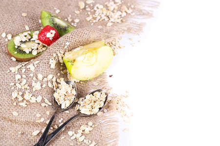 Fresh fruits with oatmeal and vintage spoons on sackcloth, isolated on white  photo