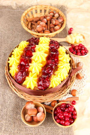 Tasty fruity homemade pie with berries and nuts, on brown background photo