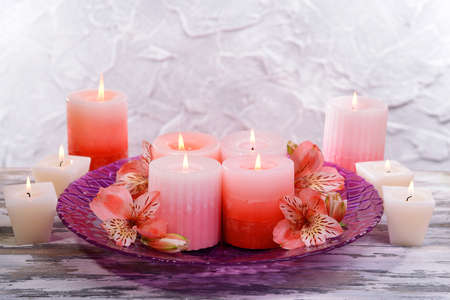 Beautiful candles with flowers on table on grey background photo