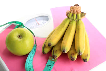 Bunch of mini bananas and measuring tape on scales, isolated on white photo