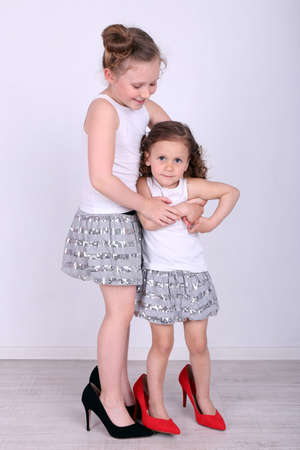 Beautiful small girls in big shoes on wall background