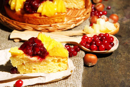 Tasty fruity homemade pie with berries and nuts, on grey wooden table photo