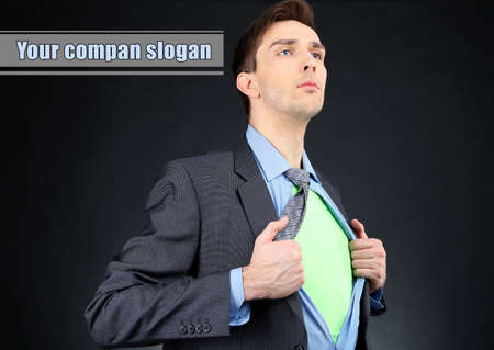 Young business man tearing apart his shirt revealing  superhero suit, on dark background photo