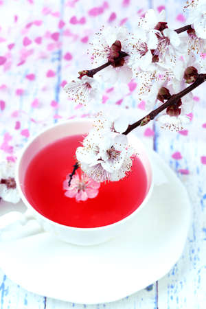 stimulated: Fragrant tea with flowering branches on wooden table close-up Stock Photo