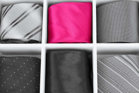 Concept of individuality.One bright color necktie among grey neckties photo