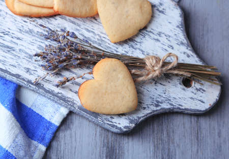 Lavender cookies on cutting board, on color napkin background photo