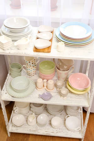 Different tableware on shelf in the interior photo