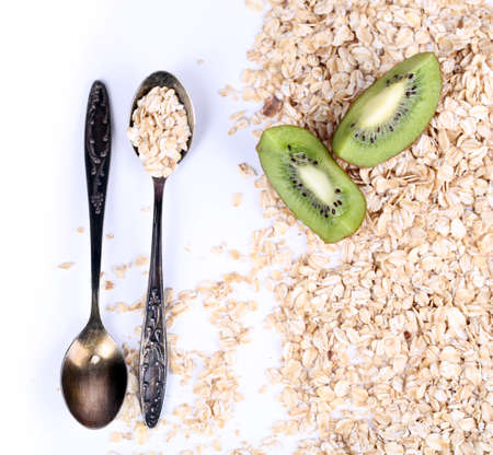Kiwi fruit with oatmeal and vintage spoon isolated on white photo