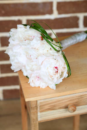 Beautiful wedding bouquet on   wooden stand on bricks background photo