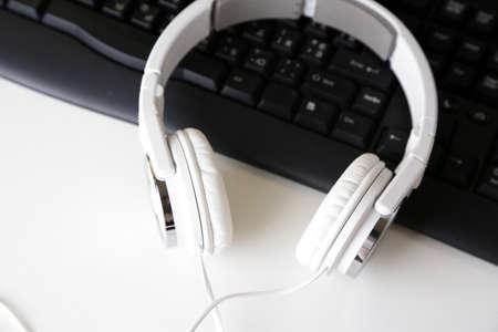 Headphone and keyboard close-up on white desk background photo