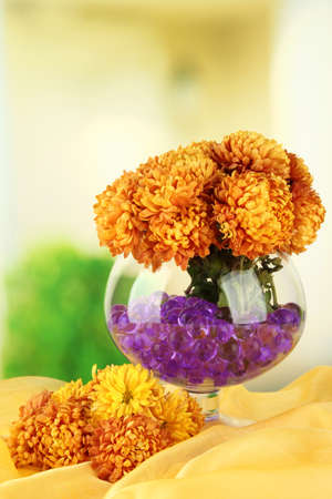 Beautiful flowers in vase with hydrogel on table on bright background photo