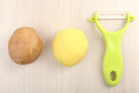 Peeler and potatoes on wooden table photo