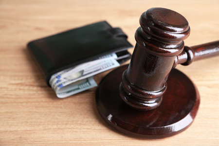 Gavel and money in wallet on wooden