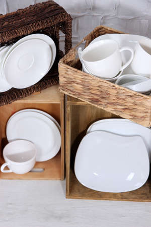 Beautiful shelves and boxes with tableware  on  light wall  photo