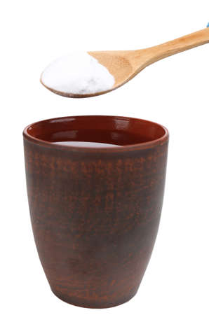 Spoon of baking soda over glass of water, isolated on white