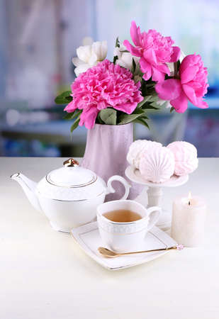 Composition of beautiful peonies in vase, tea in cup and marshmallow, on table, on light  photo