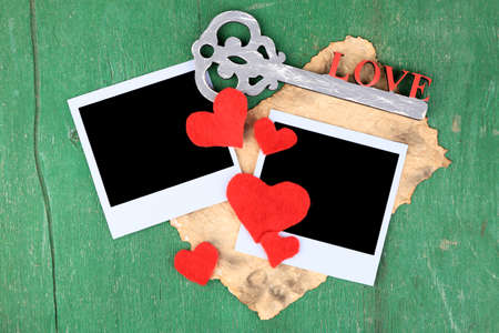 Blank old photos and decorative key, hearts on color wooden  photo