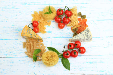 Different pasta, cheese and tomatoes on wooden table close-up photo