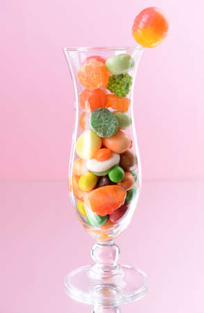 Different colorful fruit candy in glass on pink  Stock Photo