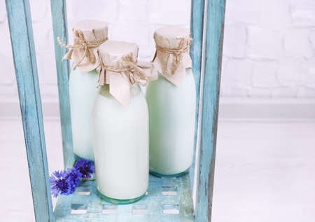 Bottles of milk and cornflowers on wooden table photo