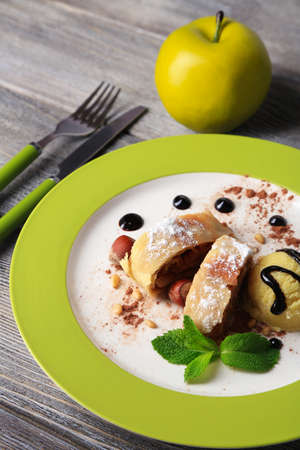 Tasty homemade apple strudel with nuts, mint leaves and ice-cream on plate, on wooden  photo
