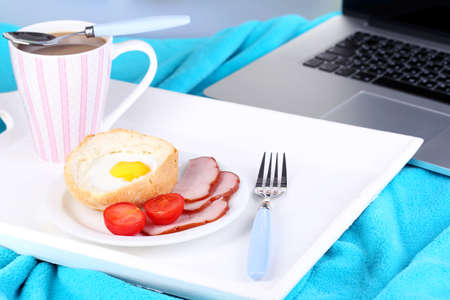 Composition with laptop and tasty breakfast on wooden tray, close-up, on bright  photo