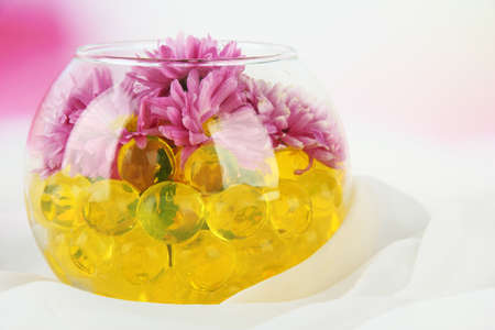 Beautiful flowers in vase with hydrogel on table on bright  photo