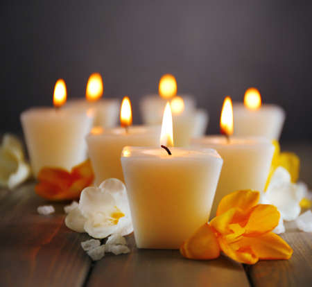 Beautiful candles with flowers on wooden  photo