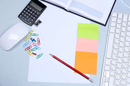 Office table with stationery accessories, keyboard and paper, close up photo