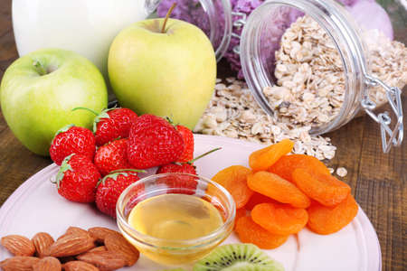 Healthy cereal with milk and fruits on wooden table photo