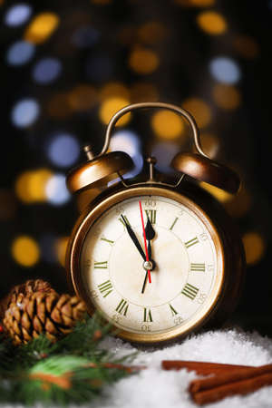 Alarm clock with snow and decoration on table on bright background photo