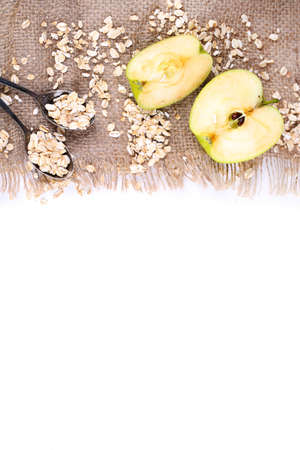 Apple with oatmeal and vintage spoons on sackcloth, isolated on white  photo