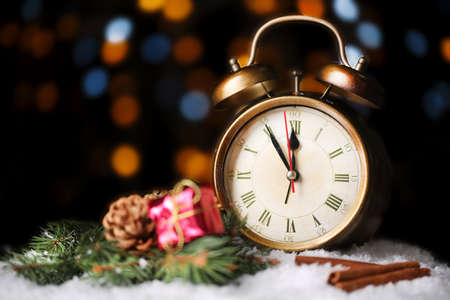 Alarm clock with snow and Christmas decoration on table on bright background photo