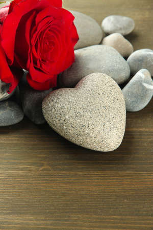 Grey stone in shape of heart, on wooden background photo