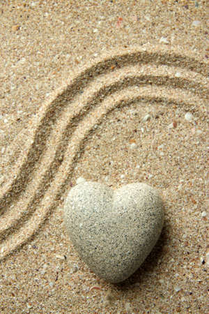 Grey zen stone in shape of heart, on sand background photo
