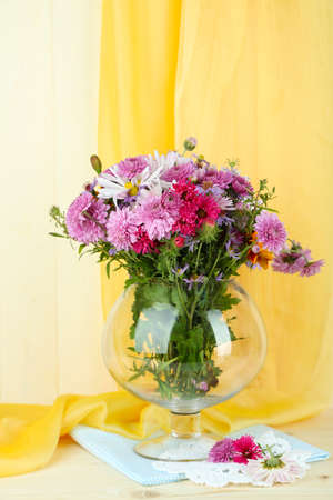 Wildflowers in glass vase on table on yellow fabric background photo