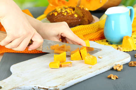 Cooking pumpkin pie on wooden table on natural background photo