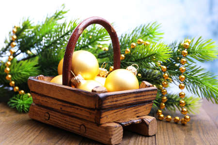 Composition with Christmas decorations in basket, fir tree on wooden table, on light background photo