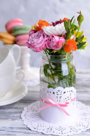 Beautiful bouquet of bright flowers in jar on table on grey background photo