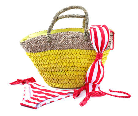 Wicker bag and swimsuit, isolated on white photo