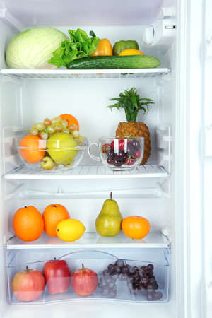 Vegetables and fruits in open refrigerator. Weight loss diet concept. photo
