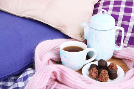 stand teapot: Cup and teapot with candies and scarf on wooden stand on bed close up Stock Photo