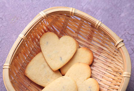 Lavender cookies in wicker basket, on color wooden background photo