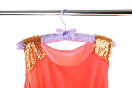Beautiful coral dress hanging on hangers isolated on white photo