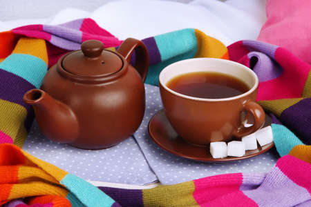 Cup and teapot with scarf on bed close up photo
