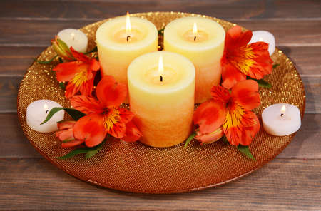 Beautiful candles with flowers on table on brown background photo