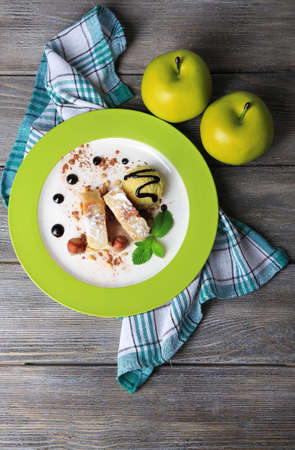 Tasty homemade apple strudel with nuts, mint leaves and ice-cream on plate, on wooden background photo
