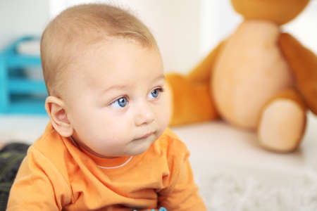 Cute baby boy lying on floor in room photo